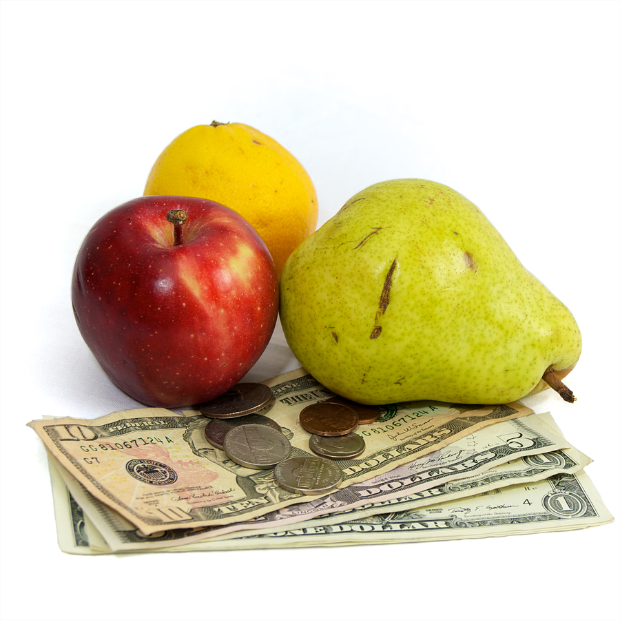 Fresh fruit on white with US currency dollars and coins as a concept for the rising costs of commodities inflation rising food costs hunger.