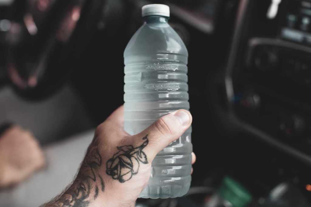 Bouteille plastique contenant de l'eau et tenue en main.